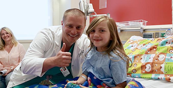 Docteur montrant les pouces vers le haut à côté du jeune patient.